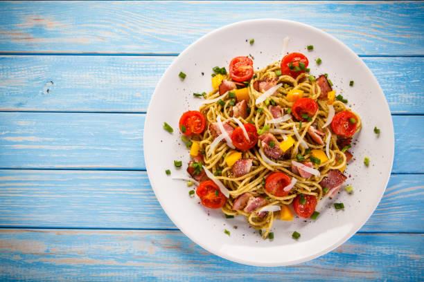 spaghetti mit gemüse und speck - gesunde huhn pasta stock-fotos und bilder
