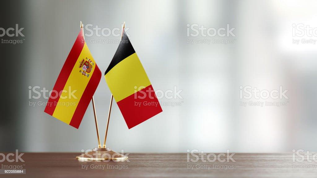 Paire de drapeau espagnol et belge sur un bureau sur fond défocalisé - Photo