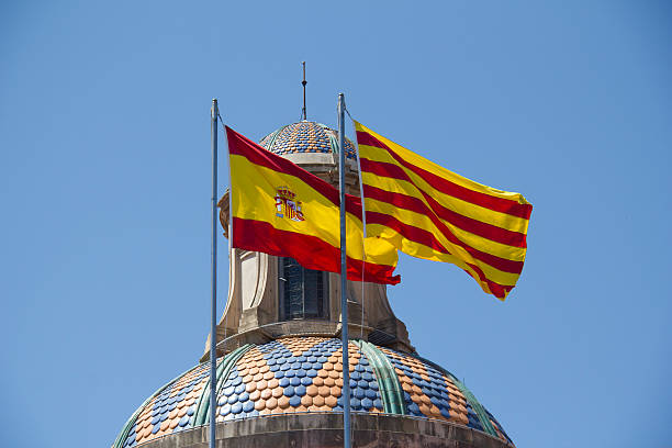 Spanish and Catalan Flag Spanish and Catalan flag flying together against blue sky on a bank building in Barcelona, Spain catalonia stock pictures, royalty-free photos & images