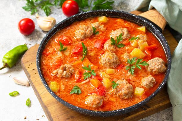 스페인 요리와 멕시코 음식 - 알본다디가스. 미트볼과 야채를 곁들인 뜨거운 스튜 토마토 수프. 스톡 사진