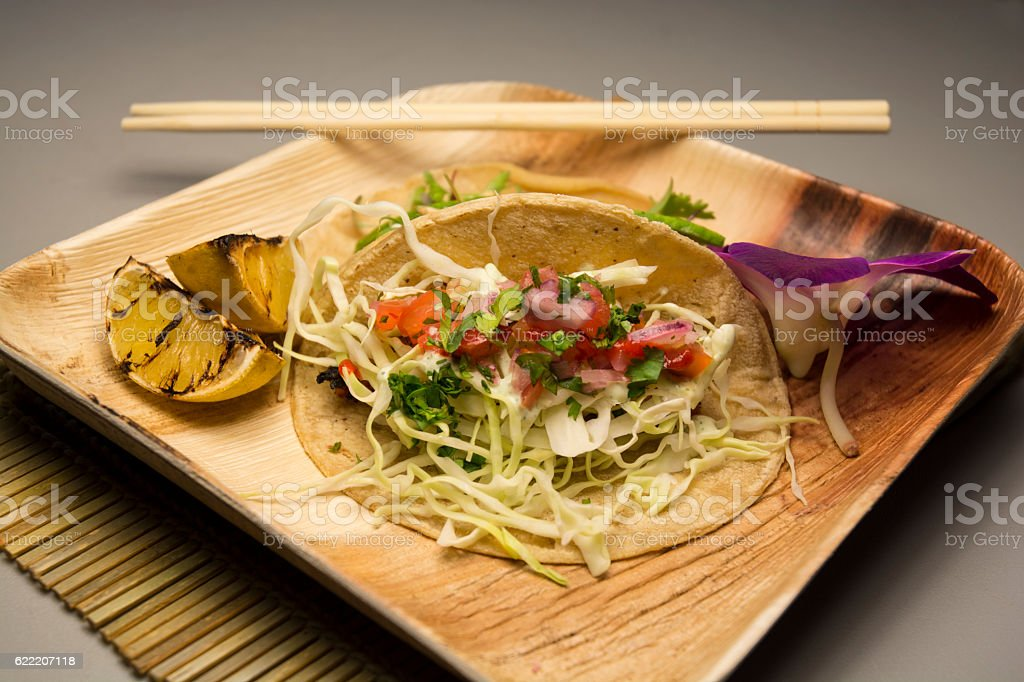 Spanish Asian Taco Meal With Lemon And Purple Orchid stock photo