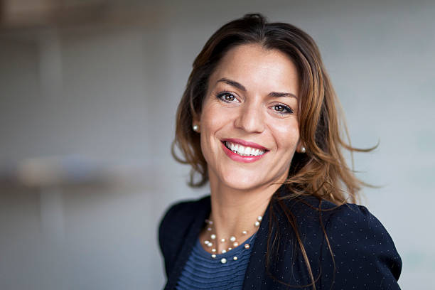 spanish businesswoman smiling at the camera. at the office. - head stock photos and pictures