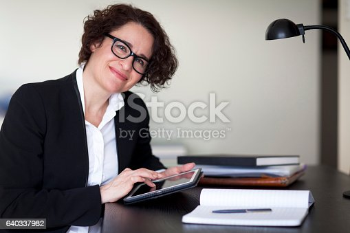 625010932istockphoto Spanish Businesswoman Smiling At the Camera. At the office. 640337982