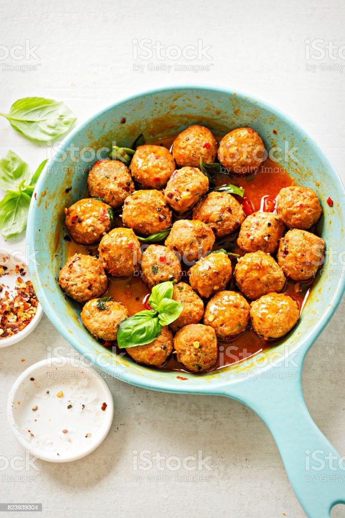 Spanish chorizo meatballs with chilli and basil on blue pan stock photo