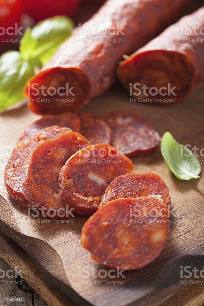spanish chorizo sausage with basil on chopping board stock photo