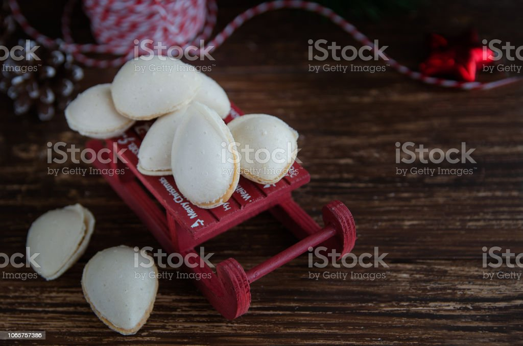 Spanish Christmas sweet - Almendras rellenas ( almond crisps filled with turron cream ) in the decorative sled with fir tree. Traditional tasty dessert in Spain. stock photo