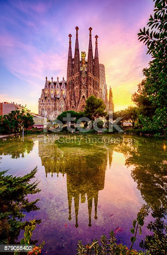 La Sagrada Familia from Antoni Gaudi at sunset  reflected in a garden pond in Plaza Gaudi. Barcelona. Spain