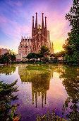 La Sagrada Familia from Antoni Gaudi at sunset  reflected in a garden pond in Plaza Gaudi. Barcelona. Spain