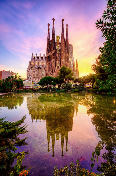 Spanish Cities Barcelona la Sagrada familia sunset clouds blue hour flare La Sagrada Familia from Antoni Gaudi at sunset  reflected in a garden pond in Plaza Gaudi. Barcelona. Spain barcelona spain stock pictures, royalty-free photos & images