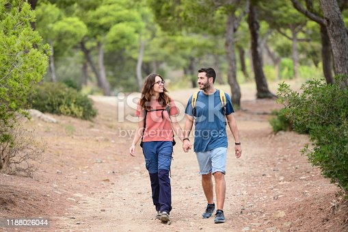 Contented young Spanish couple holding hands and enjoying healthy outdoor lifestyle as they hike through tree area of Mediterranean trail.