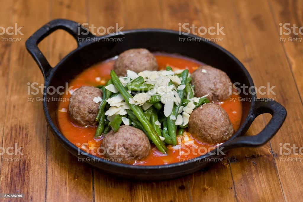 Spanish Cuisine food meatballs with green beans, almonds and tomato sauce. Hot dish in a black frying pan on a wooden table stock photo