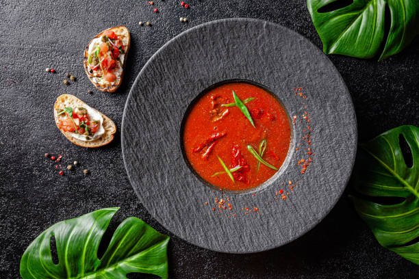Spanish cuisine. Modern cream gazpacho soup made of tomatoes, sun-dried tomatoes and basil in a black ceramic plate. Dish on a black background. background image, copy space text