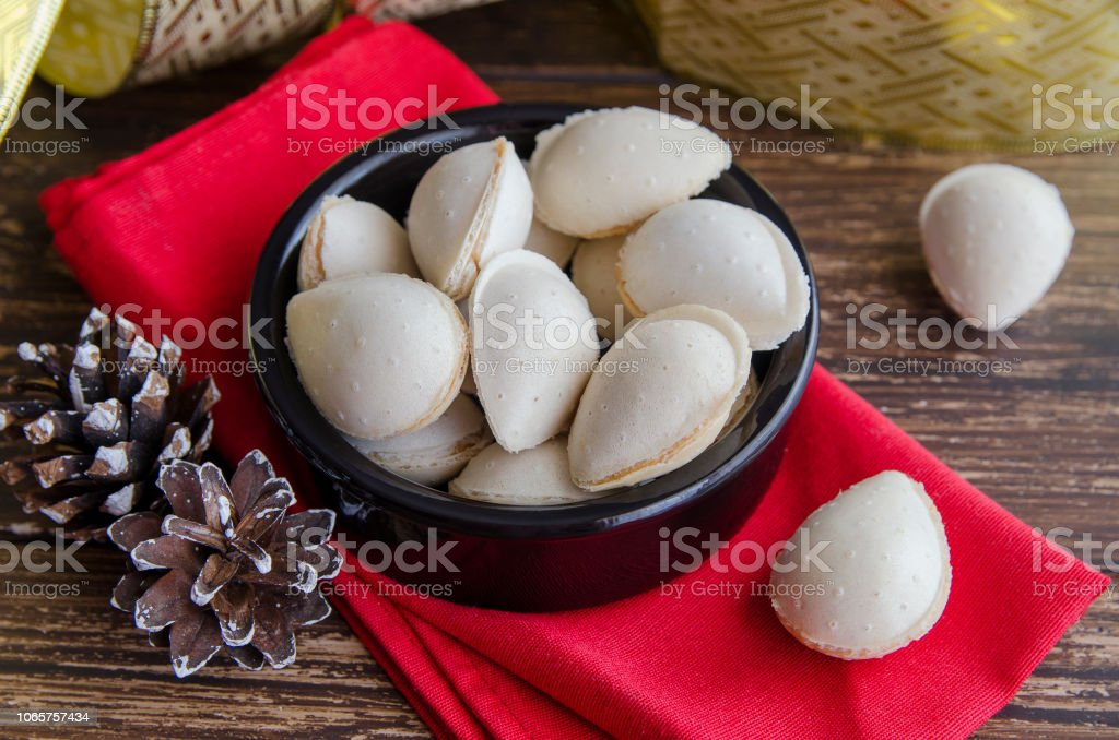 Spanish dessert, Almendras rellenas, almond crisps filled with turron cream in the ceramic bowl with christmas decoration on the table. Traditional Christmas sweets in Spain. stock photo