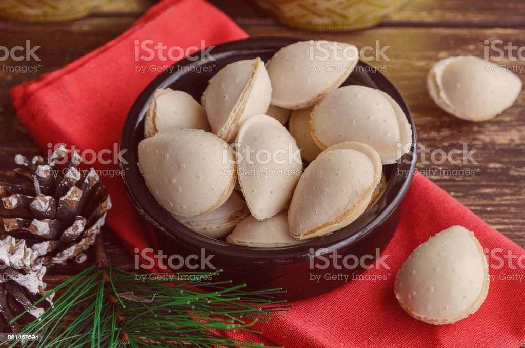 Spanish dessert, almendras rellenas, almond crisps filled with turron cream in the ceramic bowl with christmas decoration on wooden table. Traditional Christmas sweets in Spain. stock photo