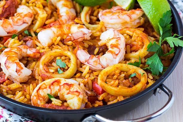 spanish dish paella with seafood, shrimps, squid, rice, saffron - paella stock photos and pictures