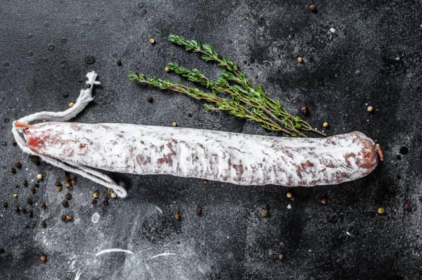 salchicha española de salami seco fuet. fondo negro. vista superior - fuet sausages fotografías e imágenes de stock