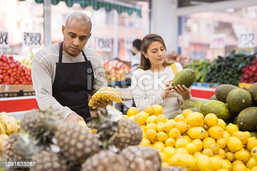 Man working  in  supermarket near  fruit  section with pineapples