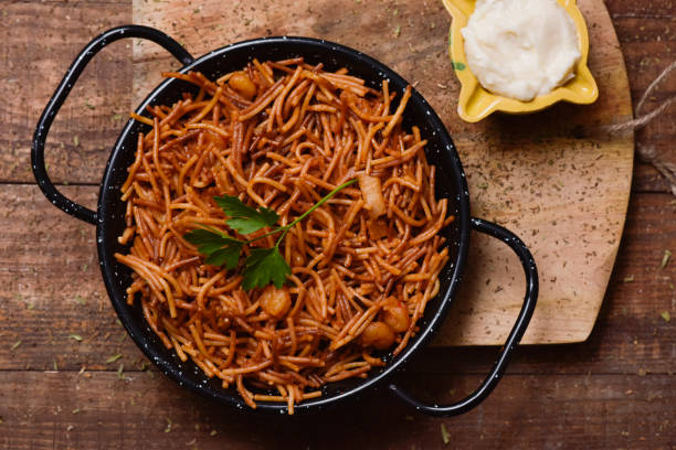 spanish fideua and aioli sauce high-angle shot of a spanish fideua, a typical noodles casserole with seafood, in a paella pan and aioli sauce in a yellow mortar on a rustic wooden table cuttlefish stock pictures, royalty-free photos & images