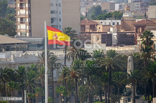 Spanish Flag flying in Gibraltar with flats and houses in the background. Gibraltar is a British Overseas Territory and headland, on Spain's south coast