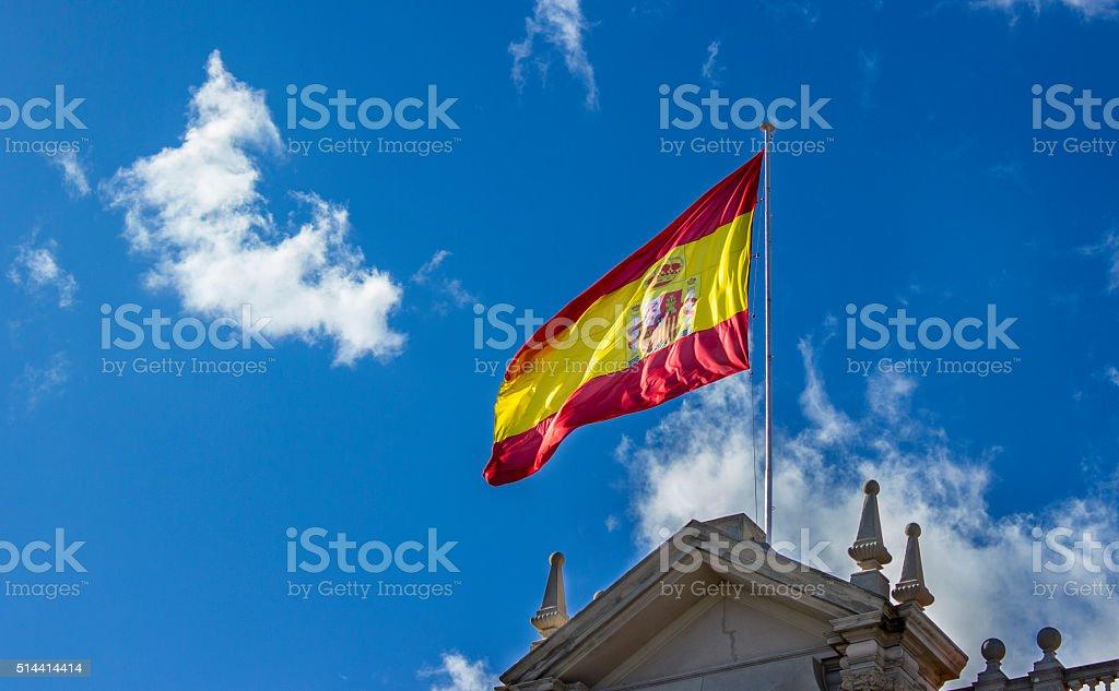 Bandeira Espanhola balançando no céu nublado - foto de acervo