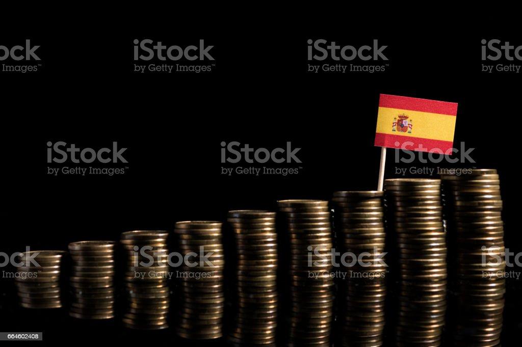 Bandeira espanhola com monte de moedas isoladas no fundo preto - foto de acervo