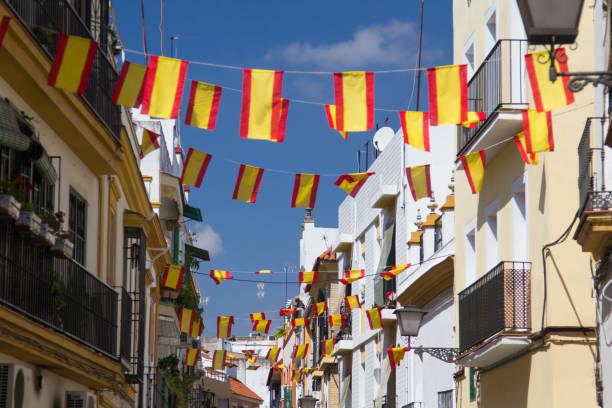 banderas españolas en la calle en sevilla, españa. detalles de la vieja fachada de edificios, pared con ventanas de marco de madera. - andalusian flag fotografías e imágenes de stock