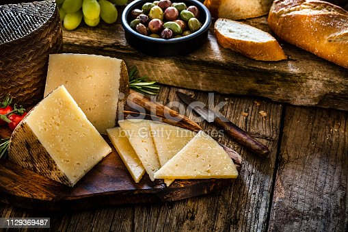 Spanish food: Manchego cheese slices and pieces in a cutting board shot on dark rustic wooden table. An old kitchen knife is beside the Manchego pieces. A bowl filled with olives, bread and green grapes are at the top of an horizontal frame. Predominant colors are brown and yellow. Low key DSRL studio photo taken with Canon EOS 5D Mk II and Canon EF 100mm f/2.8L Macro IS USM.