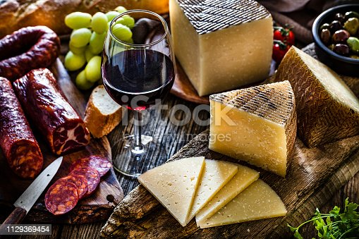Spanish food: Manchego cheese slices and pieces in a cutting board shot on dark rustic wooden table. A red wine glass is beside the Manchego pieces. Spanish chorizo is visible at the left. A bowl filled with olives, bread and green grapes complete the composition. Predominant colors are brown and yellow. Low key DSRL studio photo taken with Canon EOS 5D Mk II and Canon EF 100mm f/2.8L Macro IS USM.