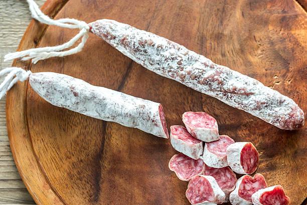 spanish fuet on the wooden board - fuet sausages fotografías e imágenes de stock