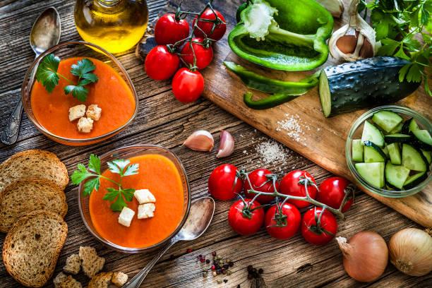 Spanischer Gazpacho und Zutaten auf rustikalem Holztisch – Foto