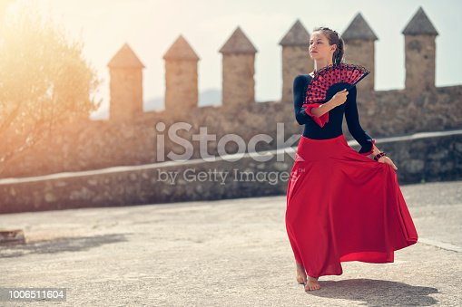 Teenage girl dressed in Spanish traditional clothes dancing on castle courtyard. Nikon D850.