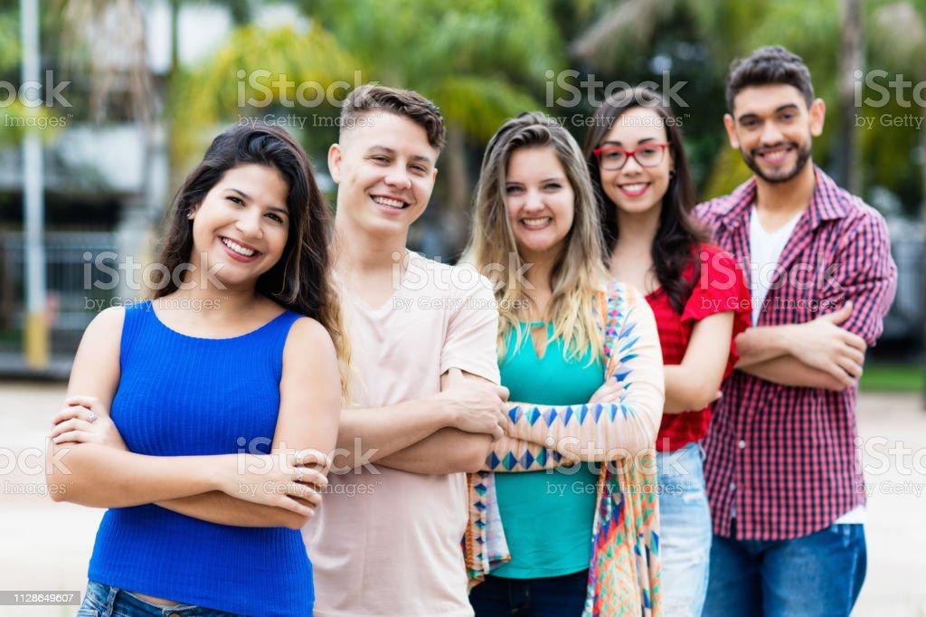 Chica española con jóvenes hombres y mujeres en línea - foto de stock