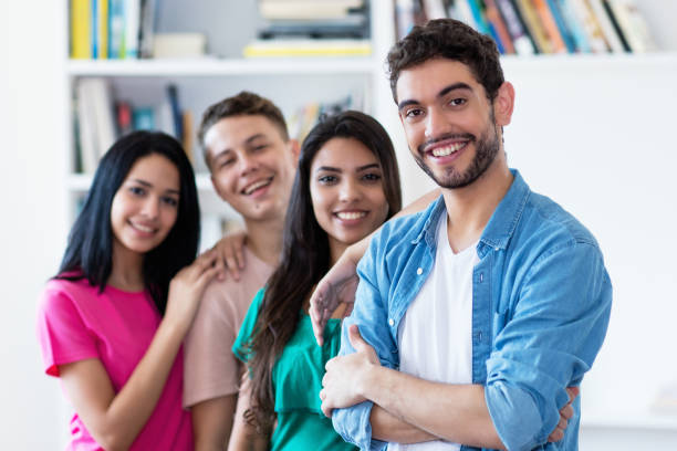 Spanish guy with group of friends in a row Spanish guy with group of friends in a row indoors at university spanish and portuguese ethnicity stock pictures, royalty-free photos & images