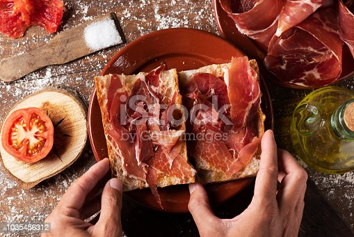 high angle view of a man preparing a typical spanish bocadillo de jamon, a serrano ham sandwich, on a rustic wooden table, next to a plate with some slices of serrano ham and a cruet with olive oil