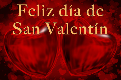 Spanish Happy Valentine's Day phrase, Feliz día de San Valentín in gold 3D letters with two red 3D hearts smaller 2D hearts are on the red coloured background