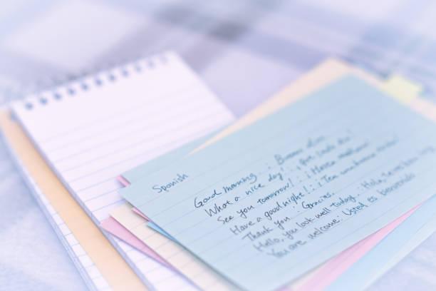 spanisch; erlernen der neuen sprache schreiben grüße auf dem notebook - teppich englisch stock-fotos und bilder