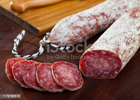 Spanish longaniza sausages cut in slices on a wooden surface, close-up