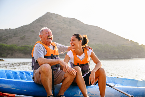 Affectionate and lighthearted senior male sitting on side of kayak with young female friend enjoying the pleasure of early morning exercise and good company.