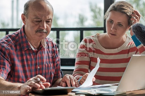 istock Spanish man counting money with his daughter. 1177485402
