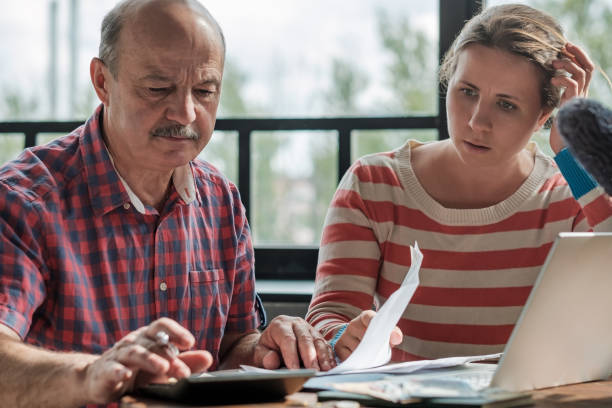 Spanish man counting money with his daughter. stock photo