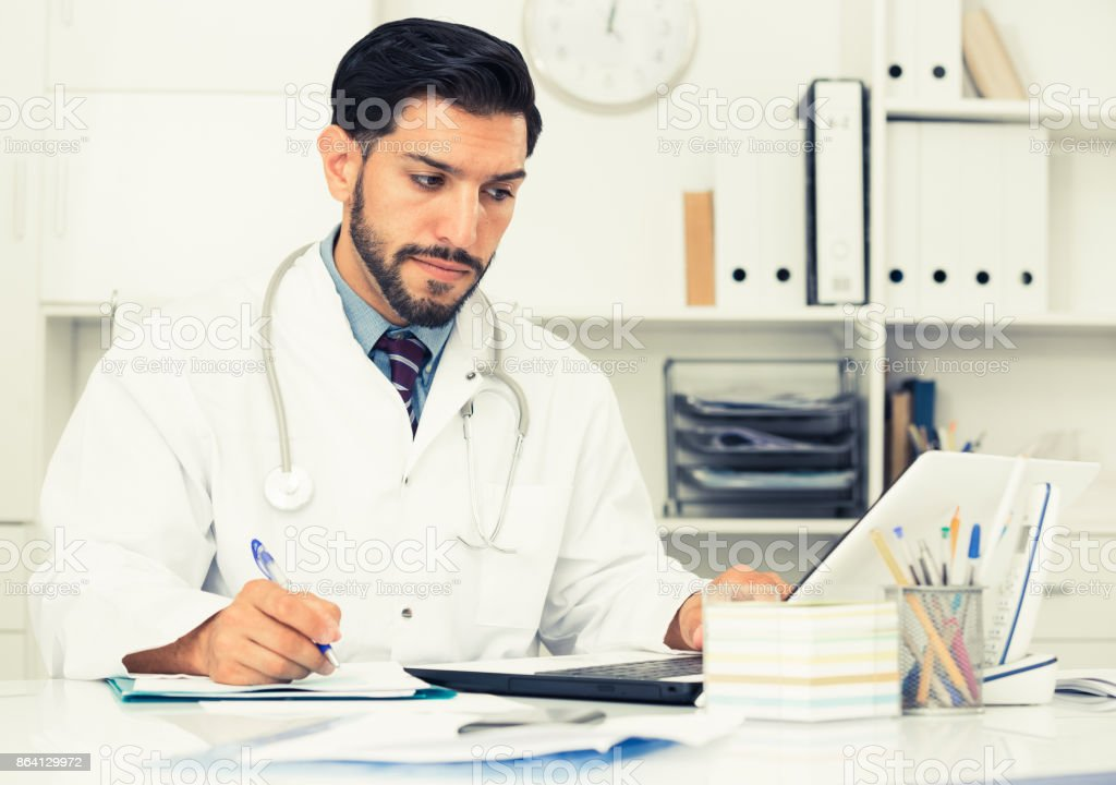 Spanish man doctor is working with documents behind laptop royalty-free stock photo