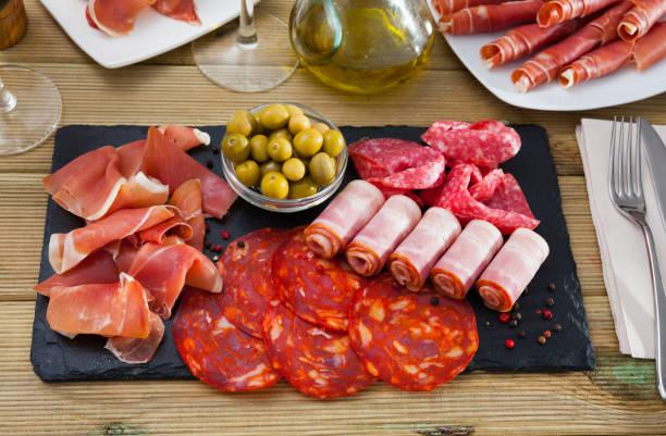 plato de antipasto cárnico español - fuet sausages fotografías e imágenes de stock