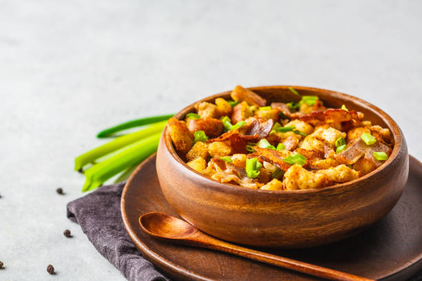 Spanish migas with pork and green onion in wooden bowl on white background. stock photo