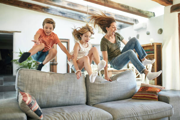 Spanish Mother and Children Jumping Over Back of Sofa stock photo