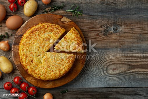 Spanish omelette with potatoes and onion, typical Spanish cuisine. Tortilla espanola. Rustic dark background. Top view with copy space.