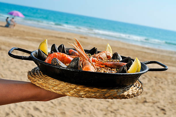 spanish paella on the beach - paella stock photos and pictures