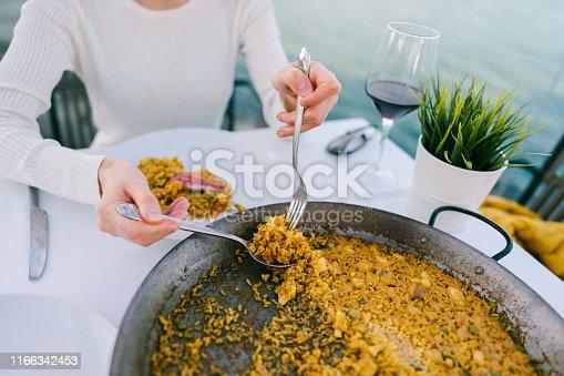 Woman in restaurant eating paella