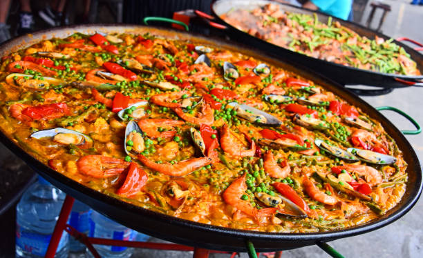 spanish paella prepared in the street restaurant - paella stock photos and pictures
