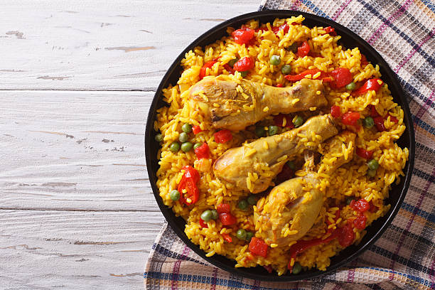 spanish paella with chicken and vegetables. horizontal top view - paella stock photos and pictures