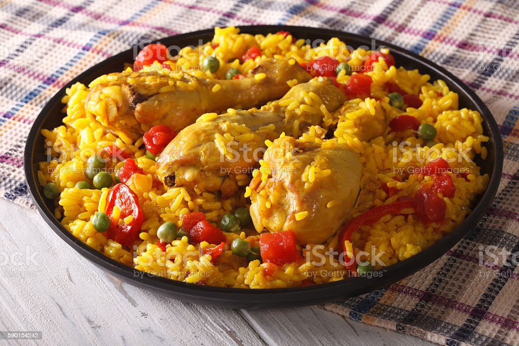 Spanish paella with chicken closeup on a plate. horizontal stock photo
